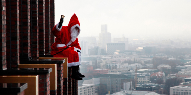 Kletternde und abseilende Weihnachtsmänner